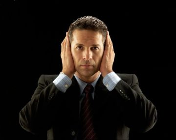 22525853 - businessman covering his ears on black background